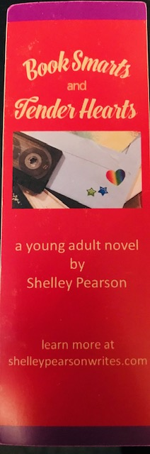 "The image is a picture of a bookmark with a red background, purple stripes at the top and bottom, and text that reads ""Book Smarts and Tender Hearts,"" ""a young adult novel by Shelley Pearson,"" ""learn more at shelleypearsonwrites.com"""
